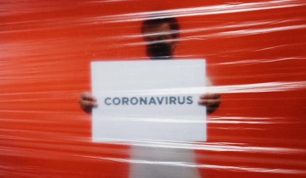 Masked man behind plastic holding Coronavirus sign